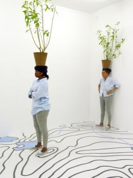 "Otobong Nkanga, ""Diaspore"", 2014, Ortsspezifische Installation und Performance 14 Rooms, Basel, Auf den Boden laminierte topografische Karte (Tintenstrahldruck), Cestrum nocturnum, Pflanzentöpfe © Otobong Nkanga, Foto: Wim van Dongen"