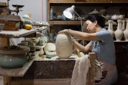 Meisterin Chen Shaoqing in ihrer Werkstatt beim Signieren einer Vase. Foto: Franca Wohlt, 2018.